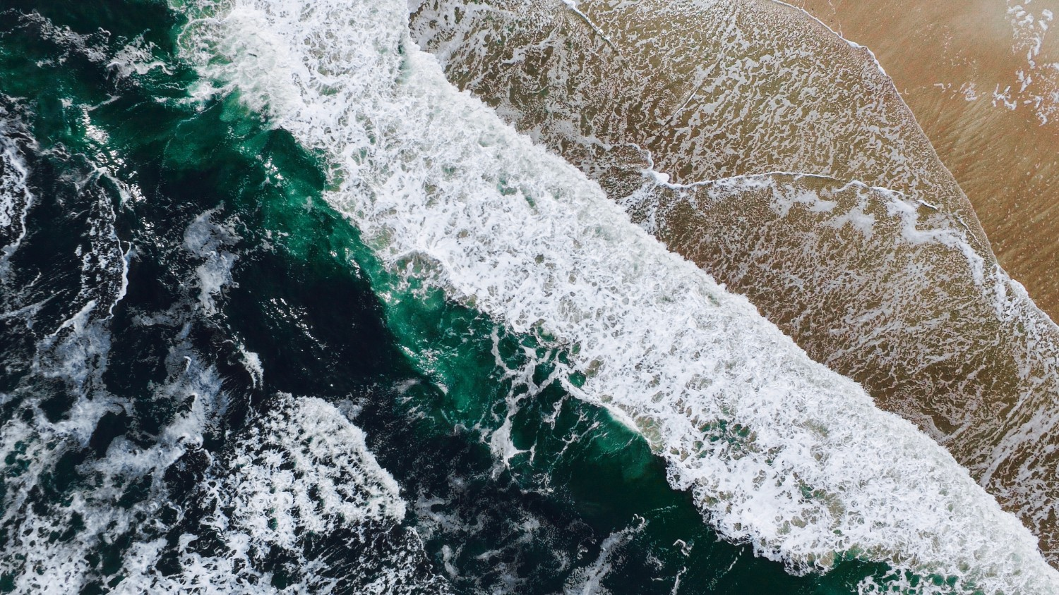 waves crashing on the shores of fernandina beach aerial view