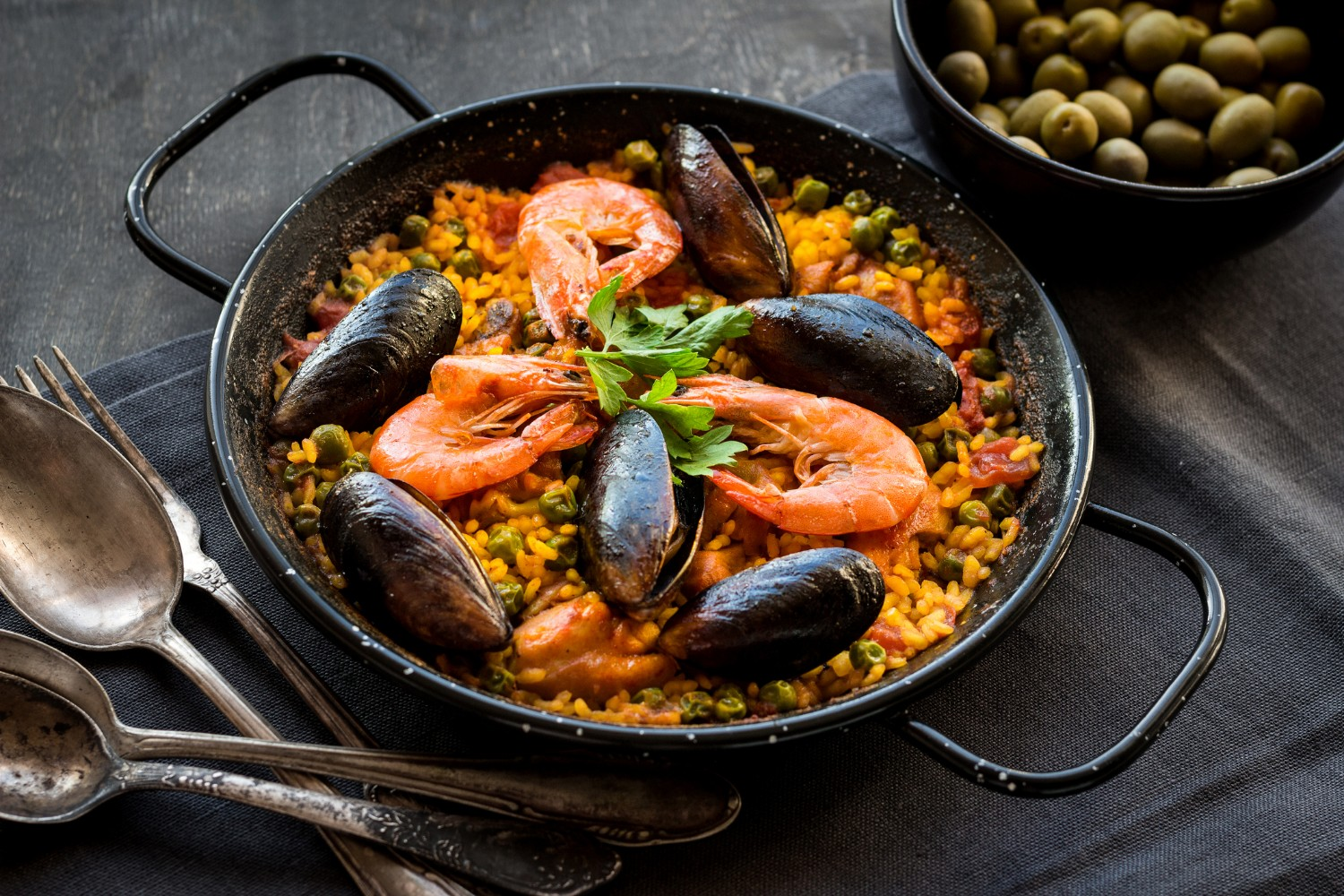Paella in black pan with rice, shrimps, mussels, squid and meat, bowl with olives and vintage cutlery. Seafood paella, traditional spanish dish. Paella on rustic black wooden table. Selective focus (Paella in black pan with rice, shrimps, mussels, squ