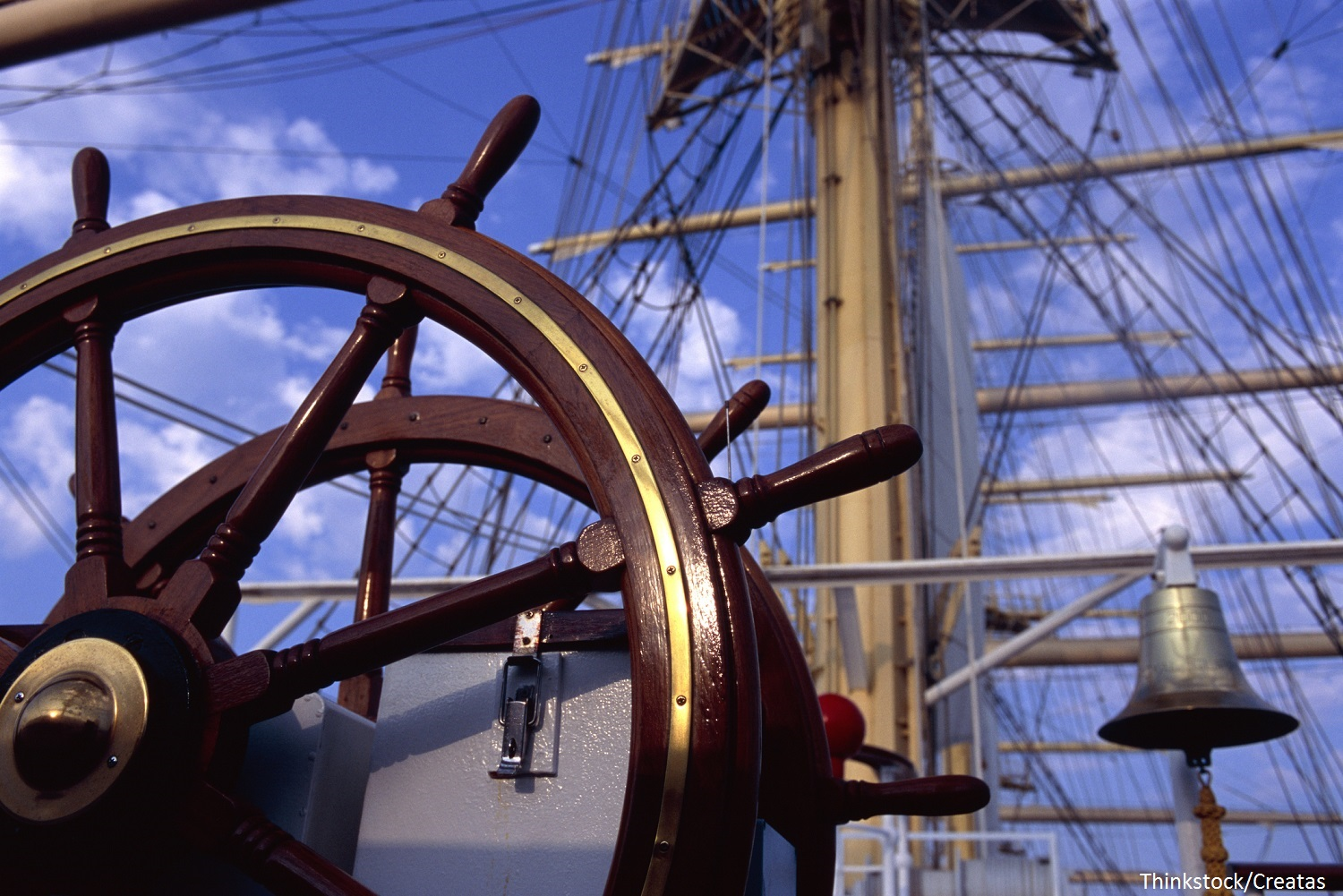 Helm and bare masts of clipper ship