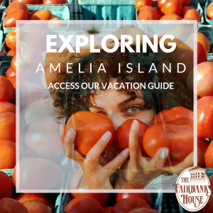 Woman holding tomatoes at an Amelia Island farmers market text reads access our vacation guide exploring amelia island