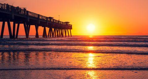 Sun rising over horizon and pier, beach illuminated with sunlight, beautiful sky reflected on the beach. Beautiful sunrise in Florida. Jacksonville Florida, USA.