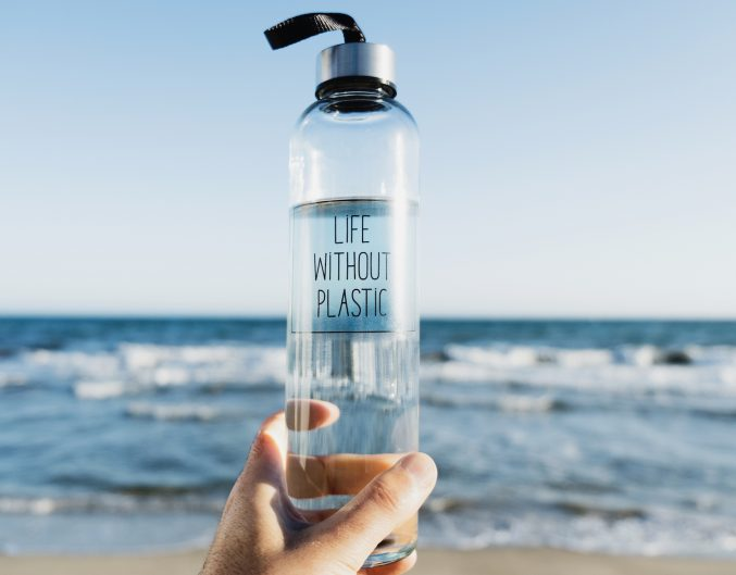 closeup of a caucasian man holding a glass reusable water bottle with the text life without plastic written in it, on the beach, with the ocean in the background (closeup of a caucasian man holding a glass reusable water bottle with the text life with