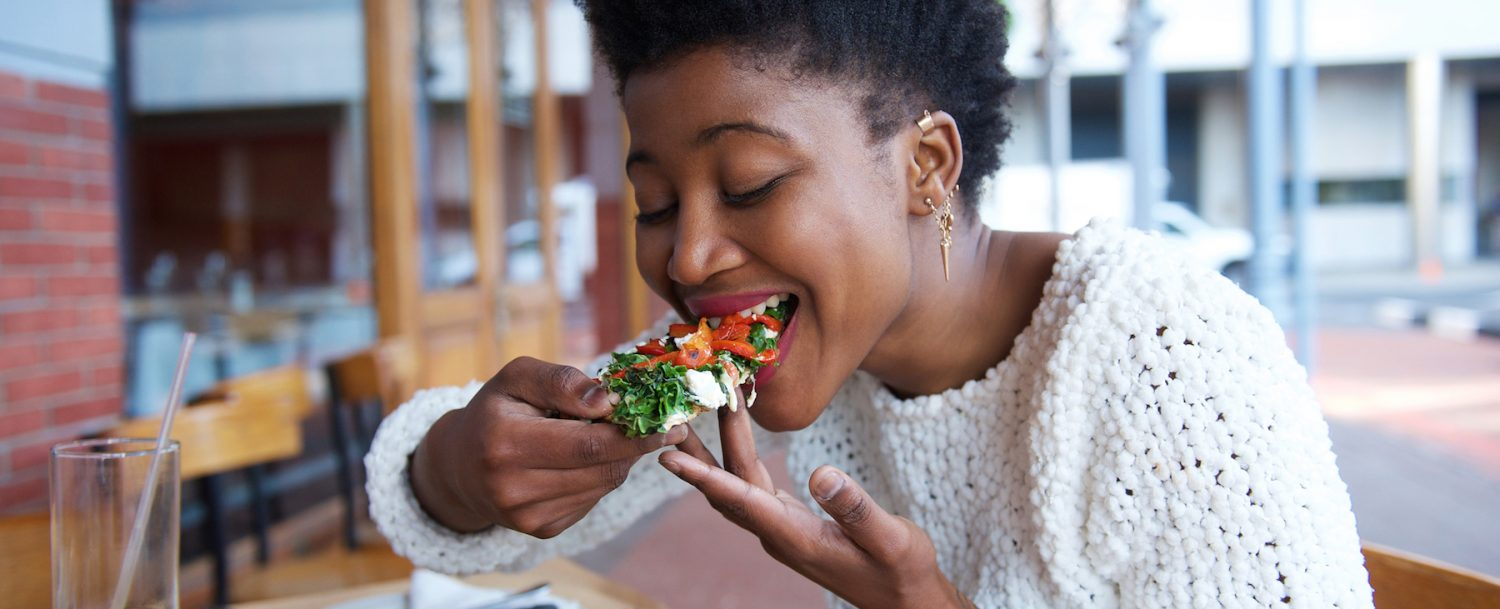 African american woman eating pizza at outdoor restaurant