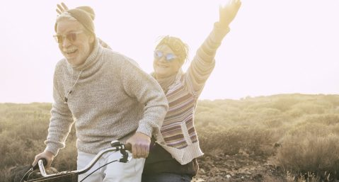 Happiness and freedom concept no limit age with old aged couple laughing smiling and having lot of fun together on a bike in outdoor leisure activity - youthful and playful people retired