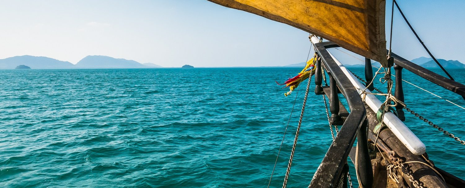 A traditional sail boat has it's sails up as it travels on the Sea towards the land in the distance. This Tall ships sails are hoisted up catching the high wind, with the beautiful clear blue sky and tropical islands in the background.