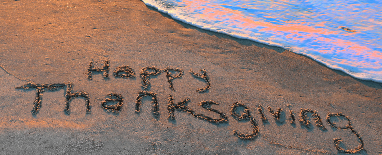 Happy Thanksgiving written on beach